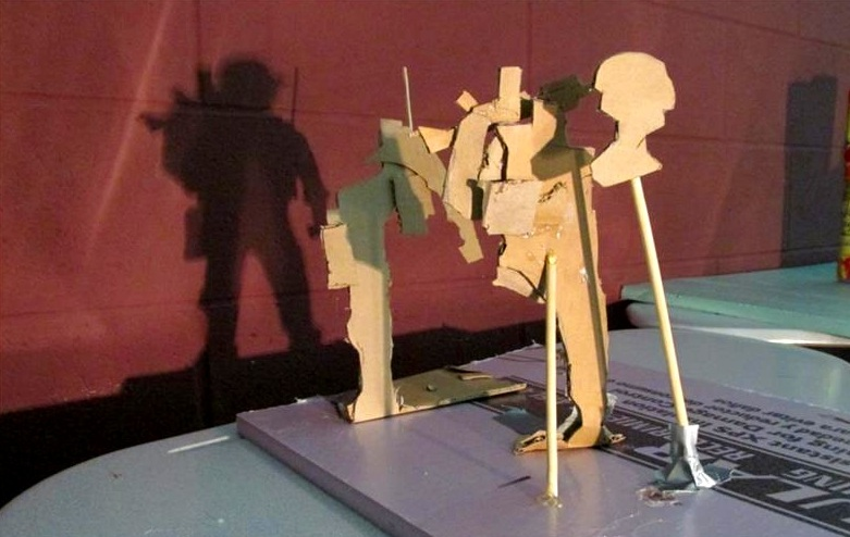 "Trash Shadow Sculpture   ""Warrior""  Cardboard, Chopsticks, Hot Glue, Construction Foam, Light Source   1' x 1' x 3'"