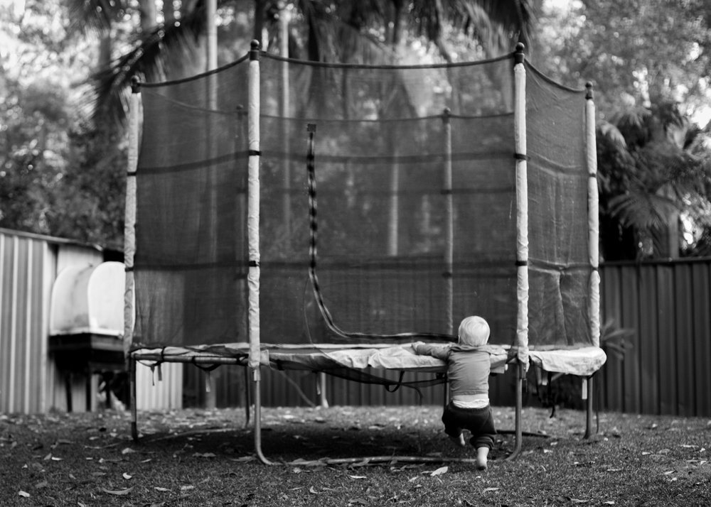 toddler trying to climb onto trampoline