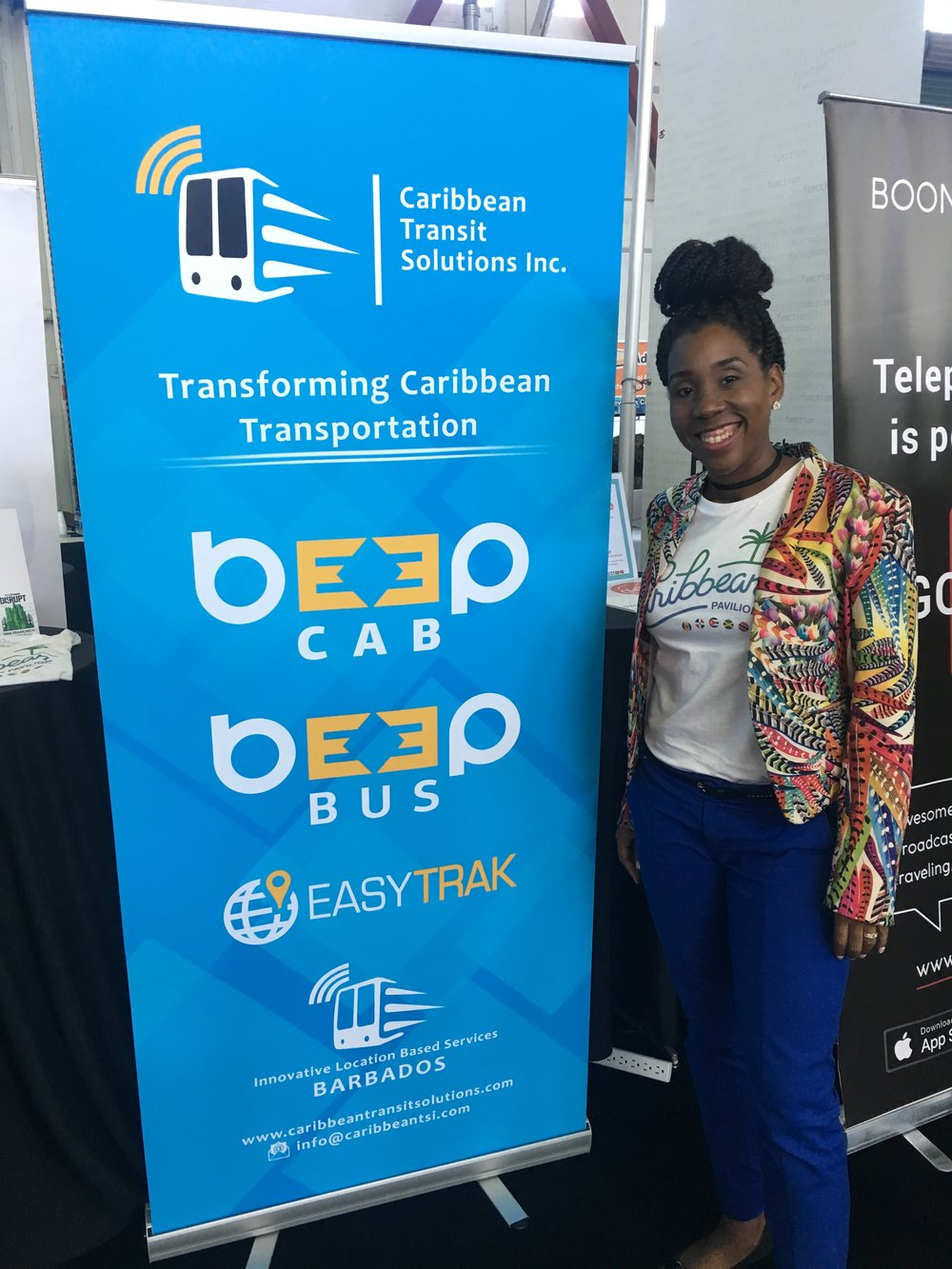 Veronica Millington, Head of Marketing at Caribbean Transit Solutions, shows off her company's banner.