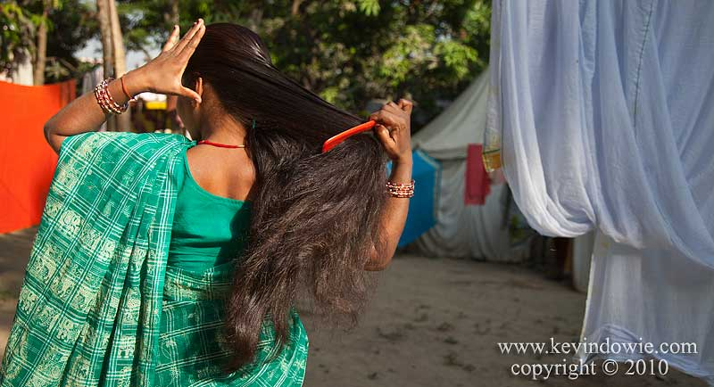 Woman brushing her hair, Haridwar, India