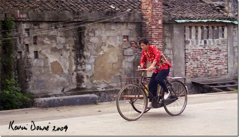 Woman riding tricycle, rural China
