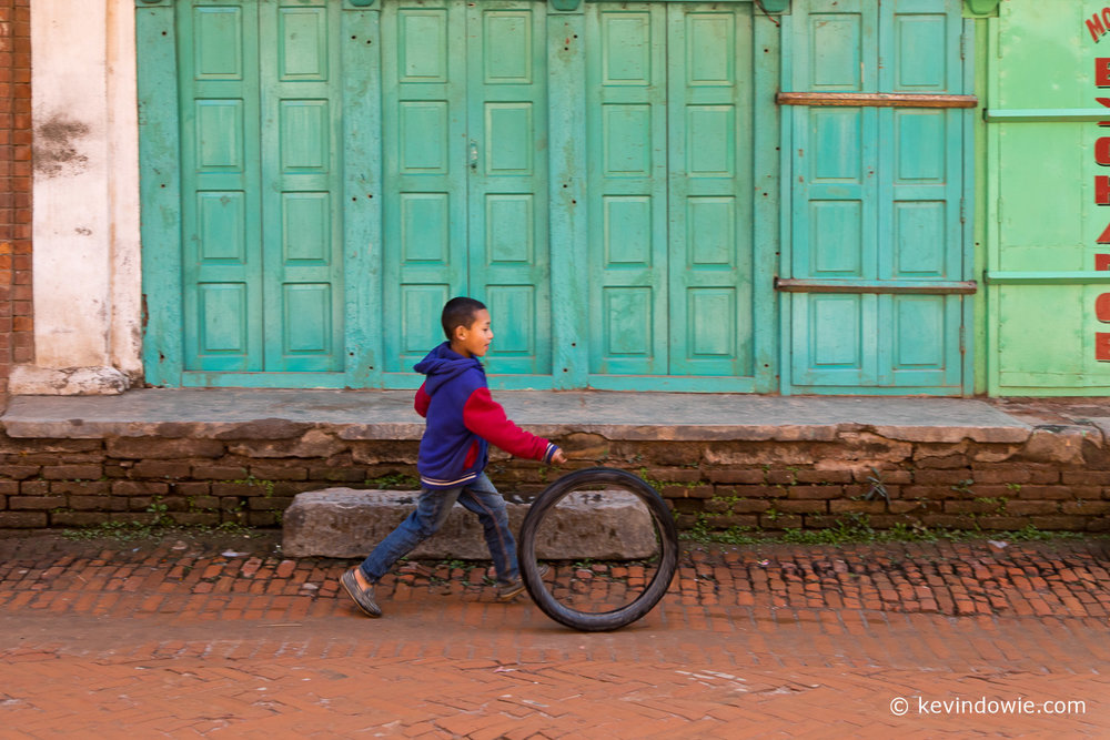 Boy playing with tyre, Kathmandu Valley, Nepal.