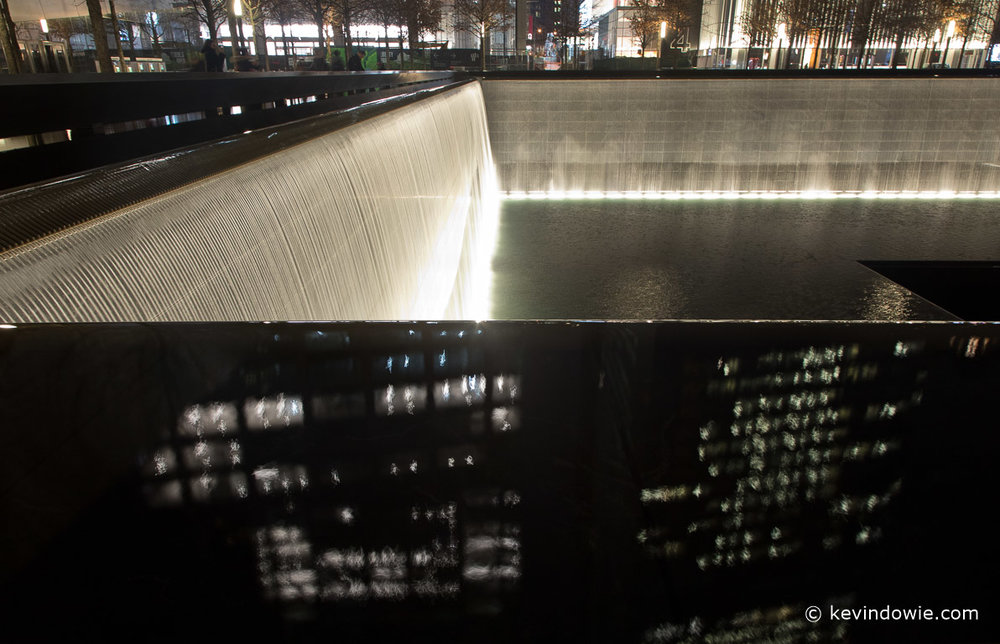 Floodlit waters spill into one of the two water features. The nearby city buildings are reflected in the waters edge.