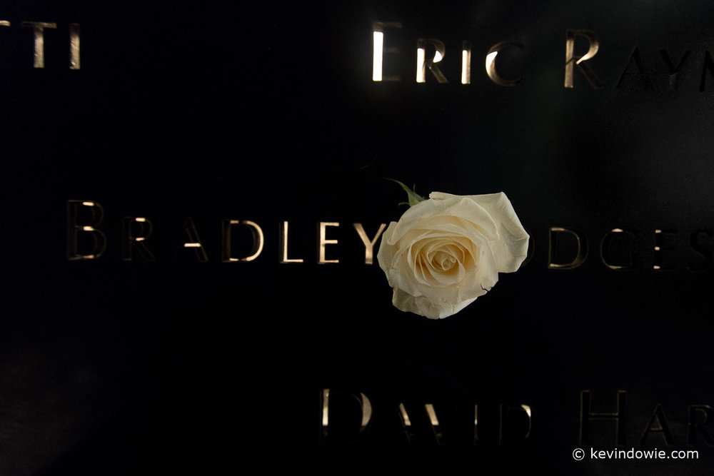 The sides of the water features include the names of those lost, punched into the black metal. There is a policy of placing a rose on the names to mark what would have been a birthday. This image was captured in the evening in very low light.