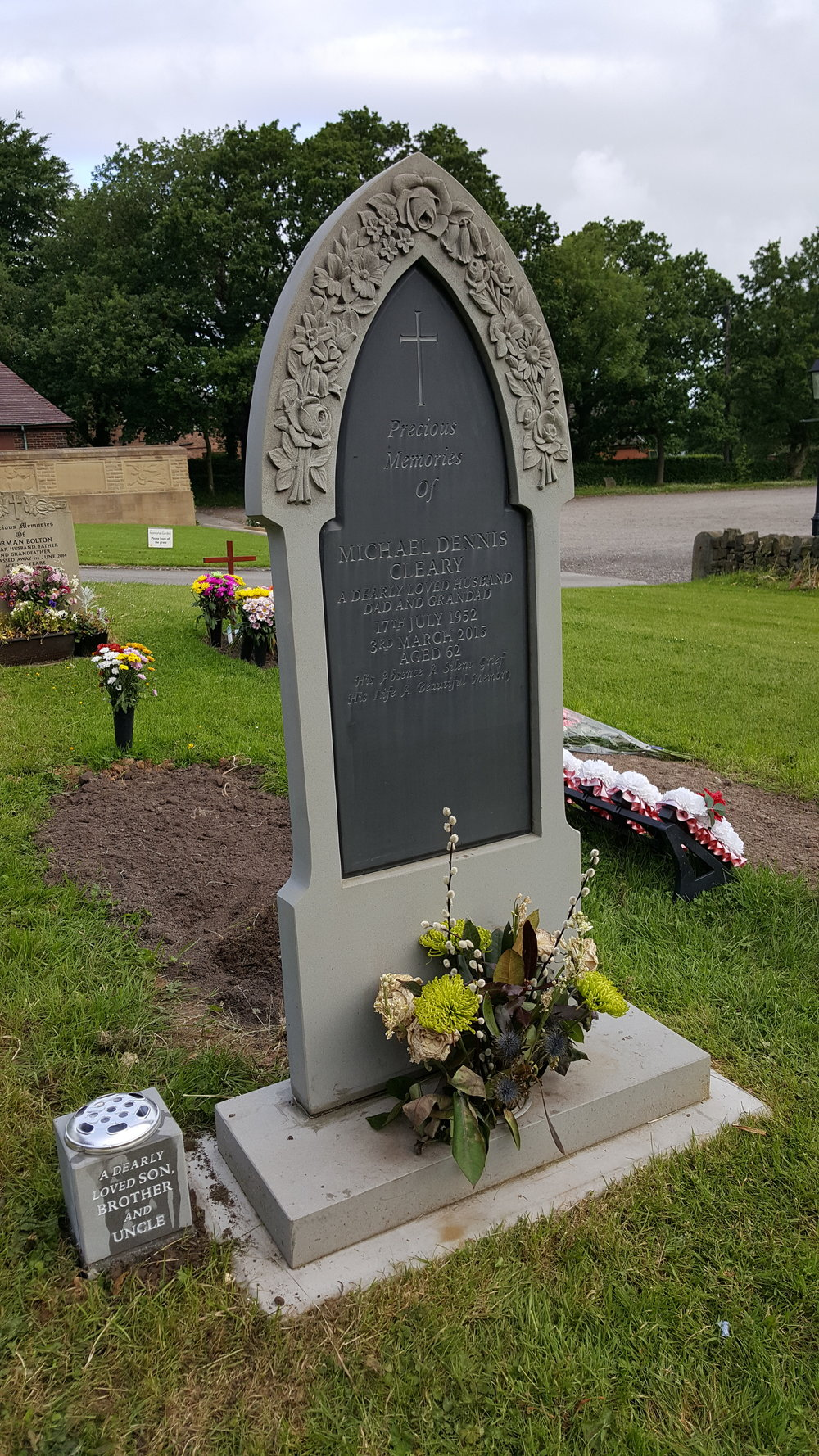 Gothic shaped large churchyard memorial with curved floral design and slate plate inlay