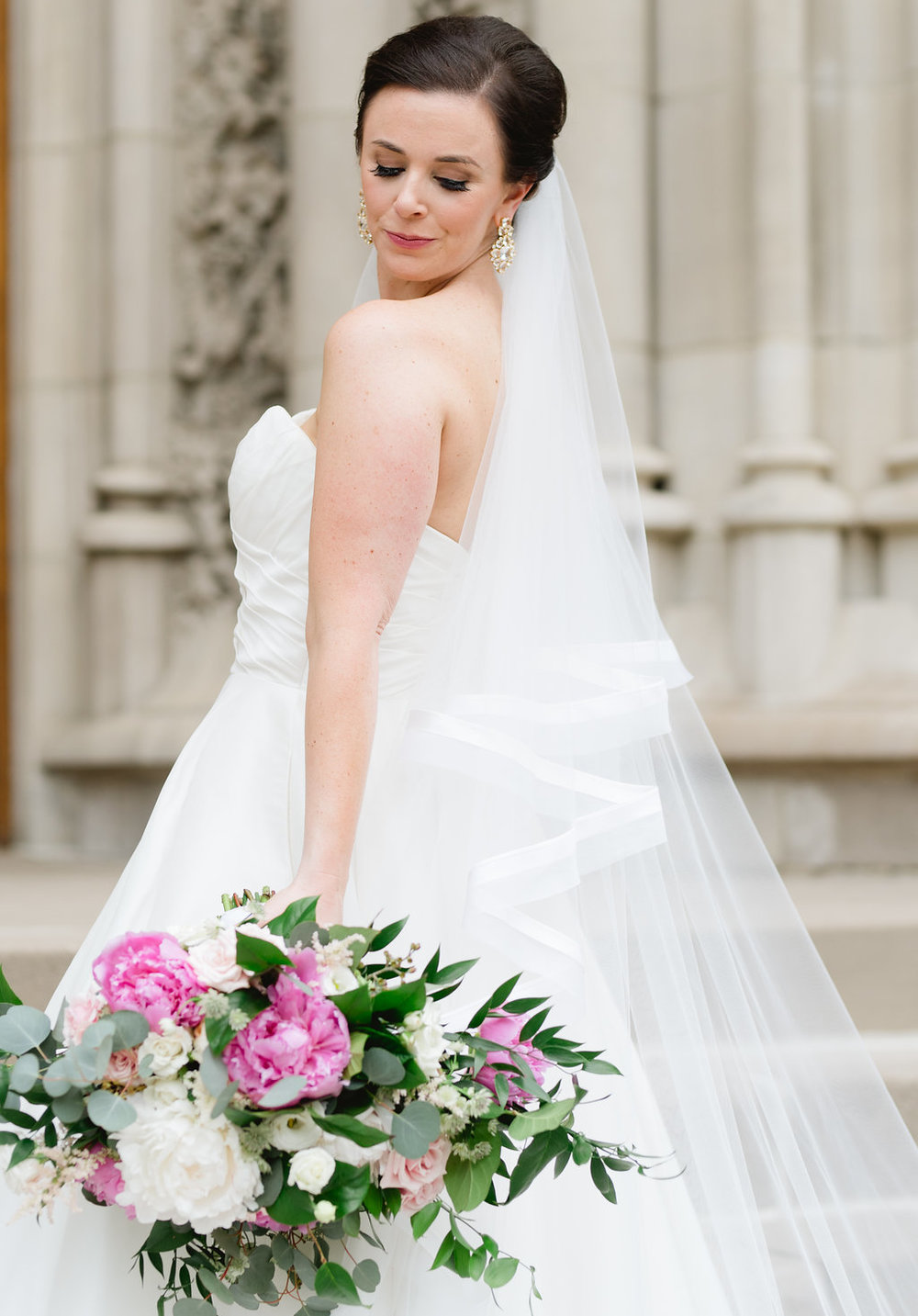 Bride in wedding dress holding pink and white wedding bouquet