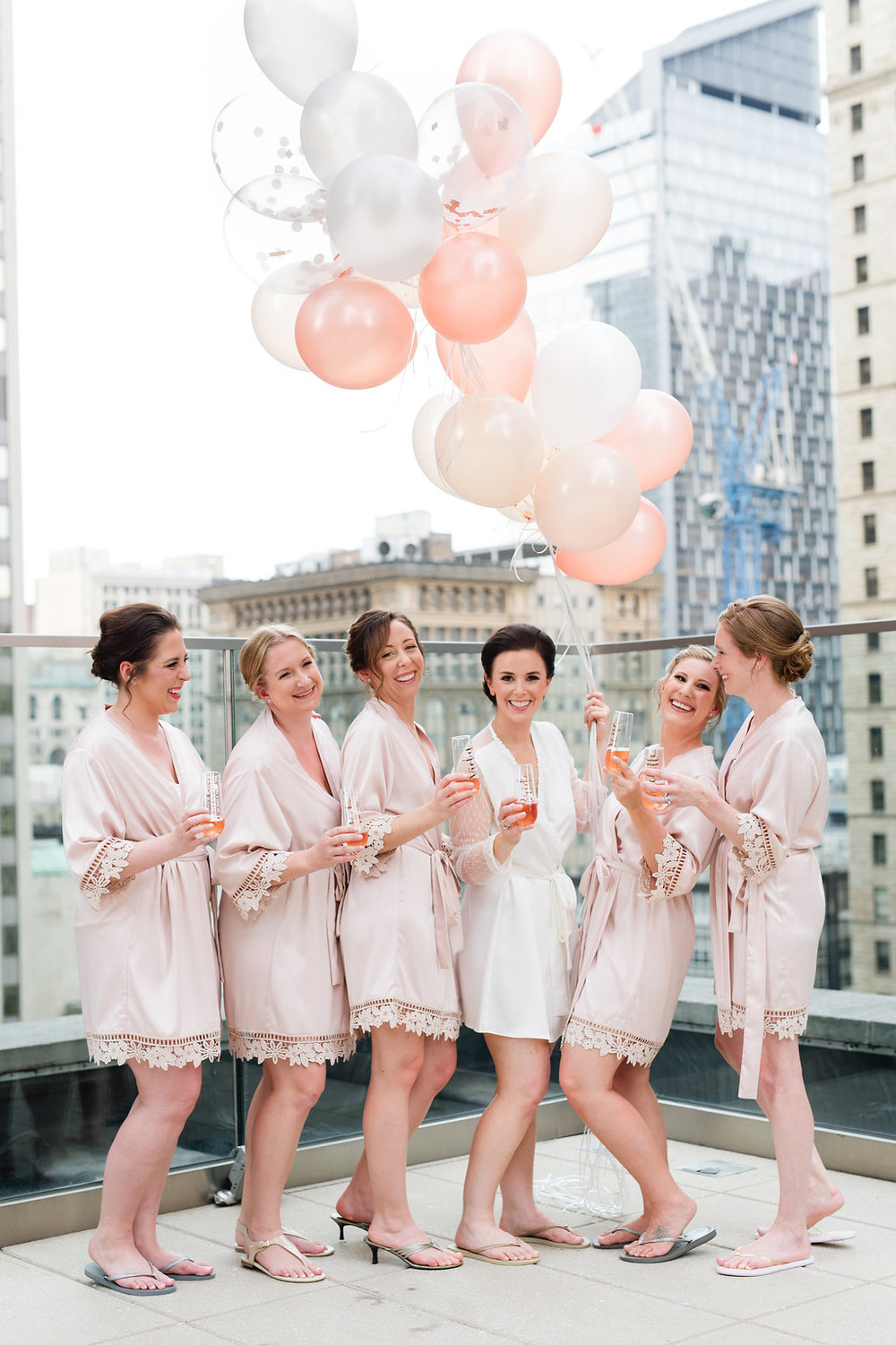 Bride with bridesmaids for champagne toast with balloons for Pittsburgh wedding at Hotel Monaco
