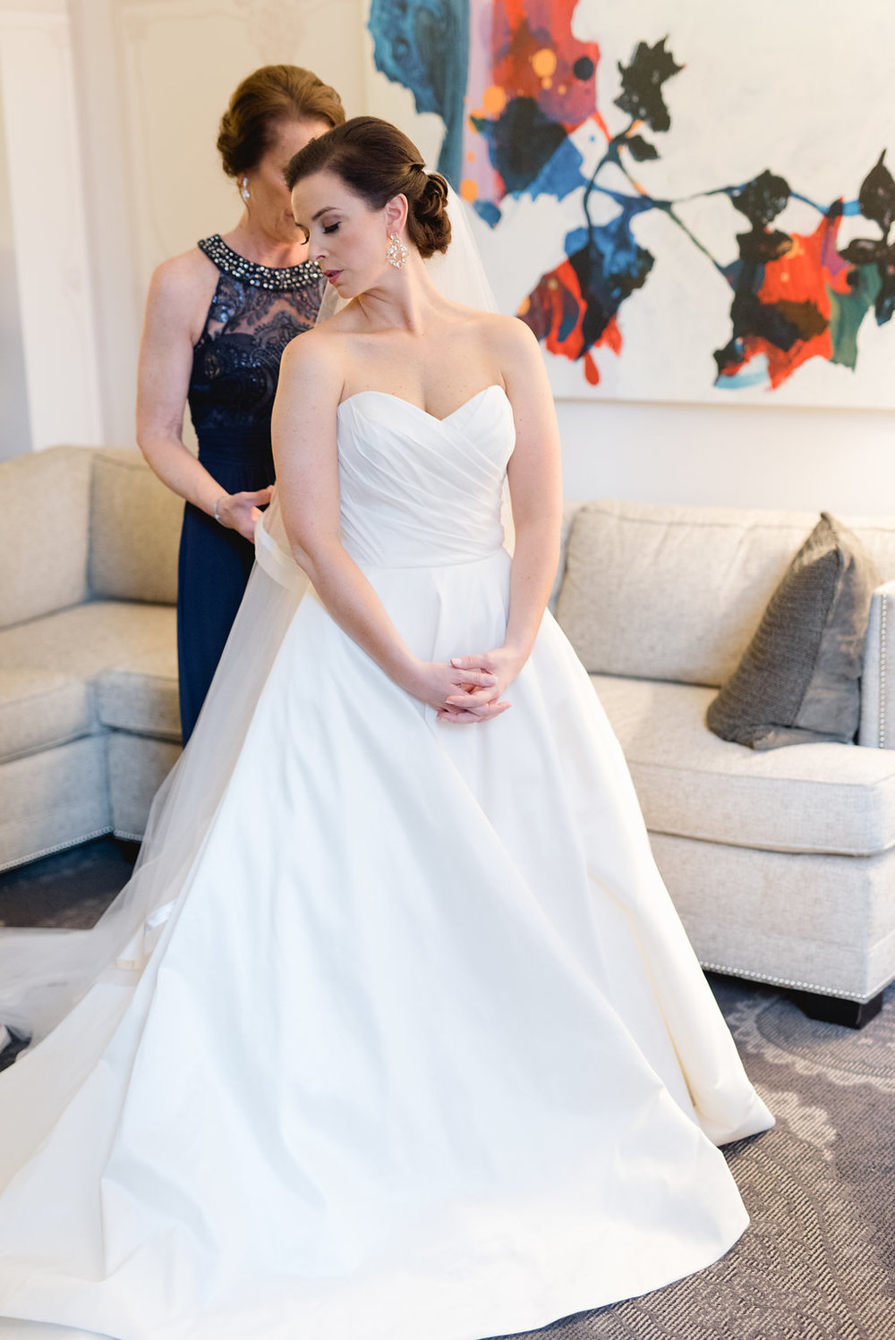 Mother of the Bride helping Bride with wedding dress for Pittsburgh wedding at Hotel Monaco
