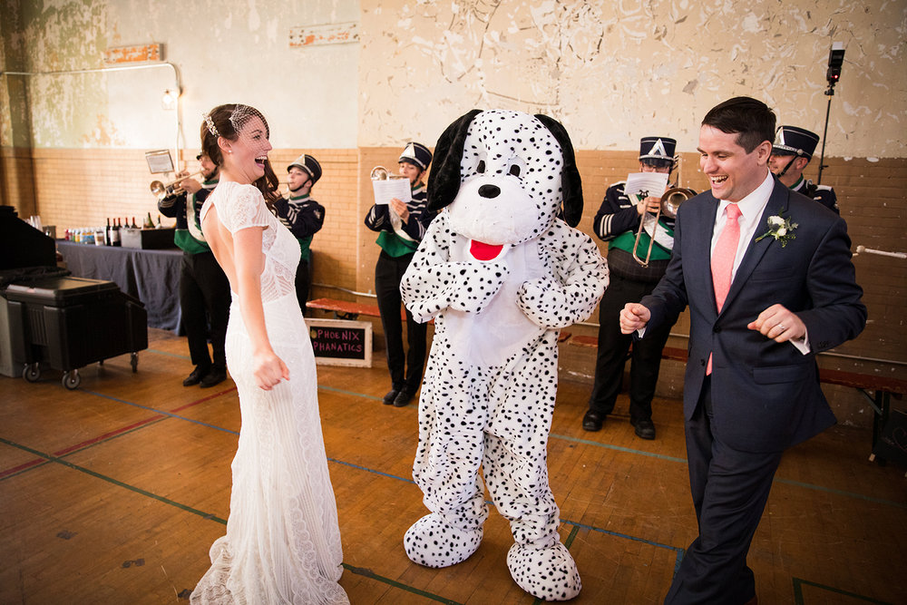 Bride and groom share a moment with mascot at their school-themed vintage glam wedding at Ace Hotel in Pittsburgh. See more fun details at exhale-events.com