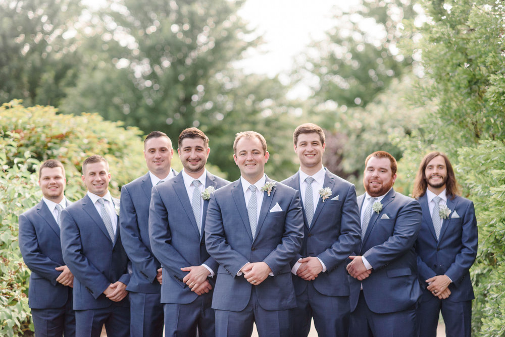 Groom and groomsmen in navy blue suits for elegant Greek wedding held in Pittsburgh at Oakmont Country Club. See more details at exhale-events.com!