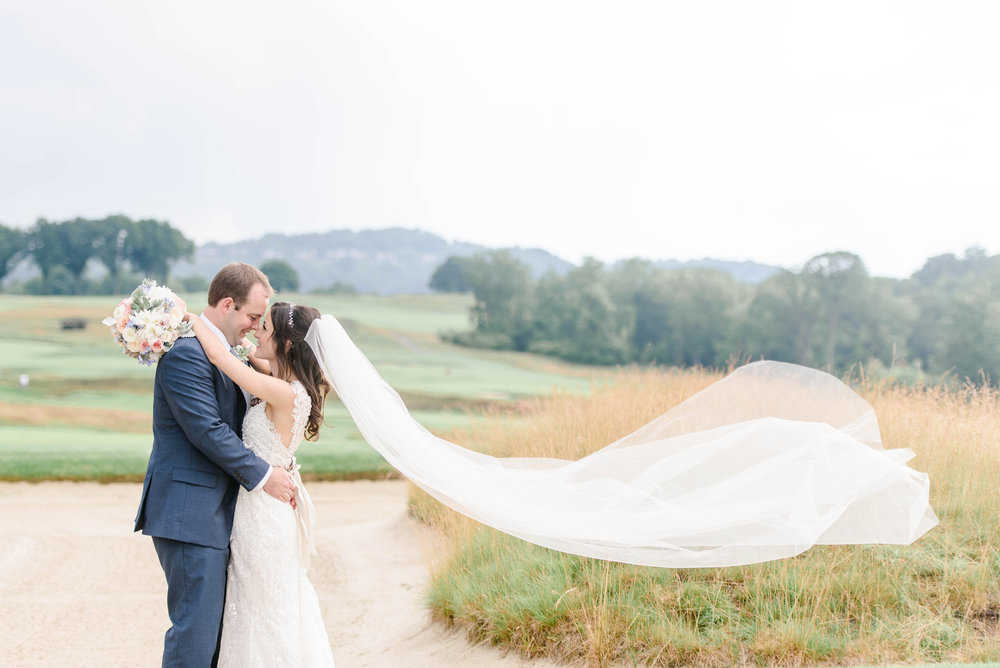 Bride's veil flying in the wind as bride and groom take wedding pictures for their sophisticated Greek wedding at Oakmont Country Club in Pittsburgh planned by Exhale Events.