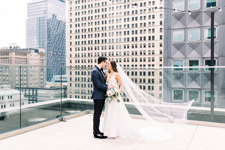 Bride and groom take wedding photo before Pittsburgh wedding at Hotel Monaco for soft pink and gold wedding