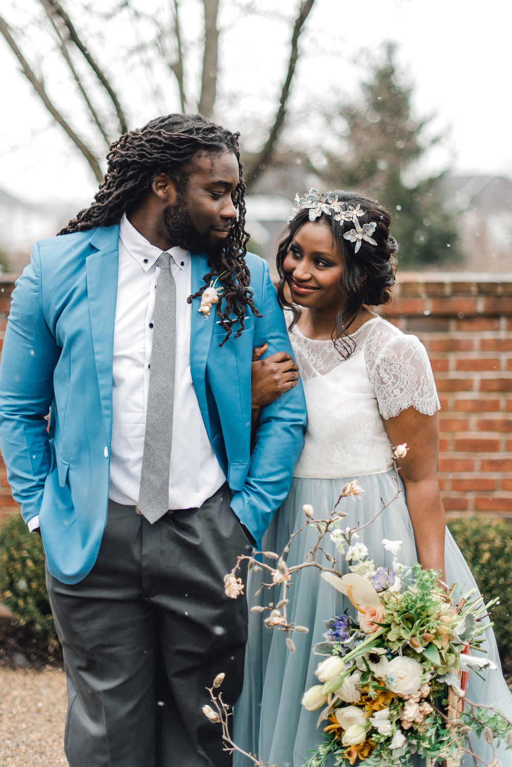 Bride and groom pose for outdoor wedding photos as it snows at wedding venue for Pablo Neruda enchanting garden styled shoot planned by Exhale Events. Get inspired at exhale-events.com!