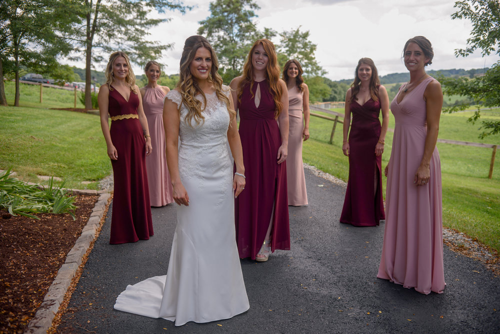 Bride and bridesmaids in pink and burgundy dresses pose for wedding photos at Pittsburgh wedding planned by Exhale Events. Find more wedding inspiration at exhale-events.com!
