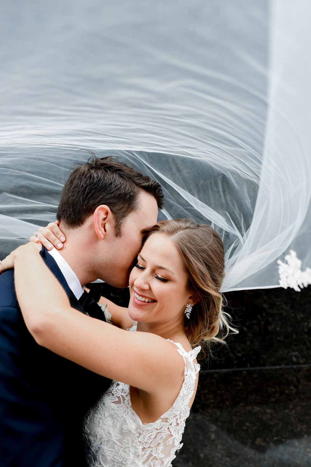 Bride and groom pose for wedding pictures outside with bride's veil flowing in the wind at Buffalo, NY wedding planned by Exhale Events. Find more wedding inspiration at exhale-events.com!
