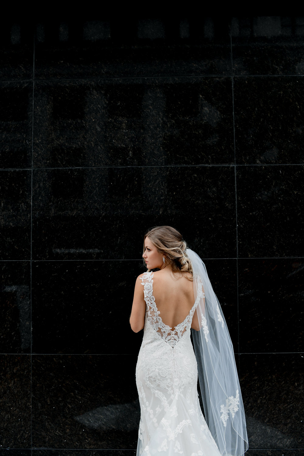 Bride poses showing wedding dress details at Buffalo, NY wedding planned by Exhale Events. Find more wedding inspiration at exhale-events.com!