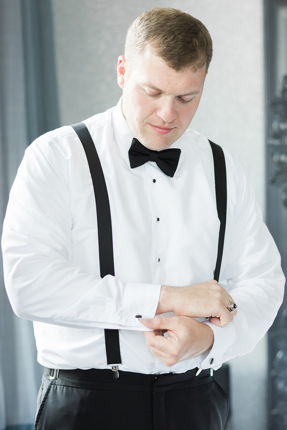 Groom getting ready in black tuxedo and bow tie for Pittsburgh wedding at PNC Park planned by Exhale Events. Find more wedding inspiration at exhale-events.com!