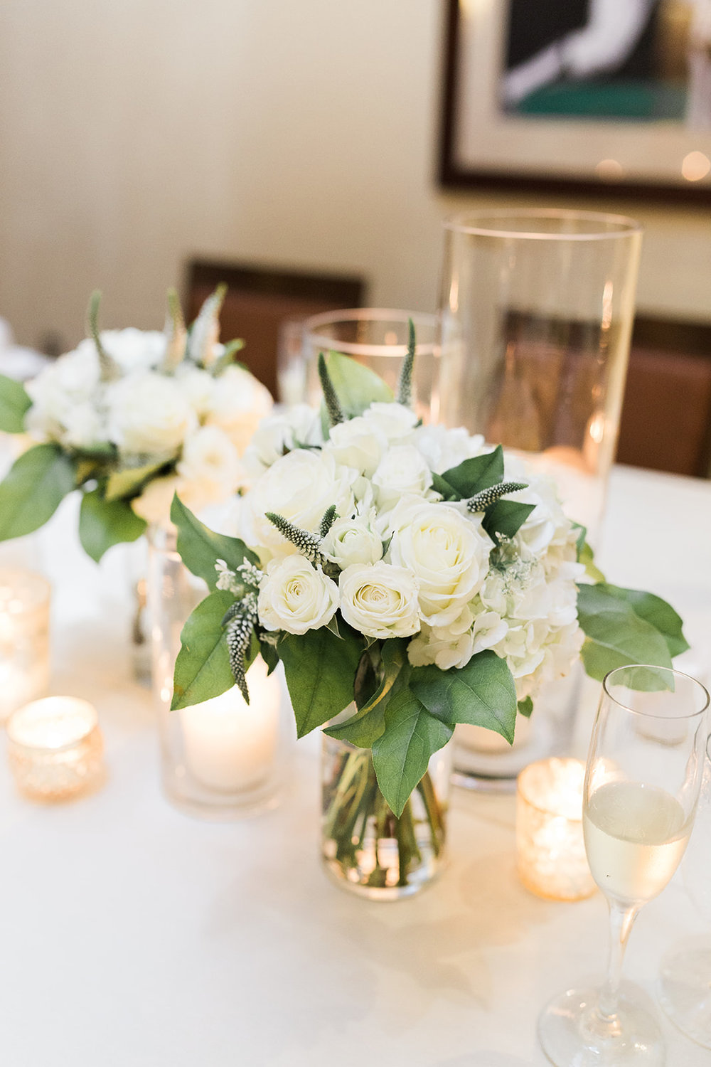Low wedding centerpieces with white flowers and candles for Pittsburgh wedding at PNC Park planned by Exhale Events. Find more wedding inspiration at exhale-events.com!