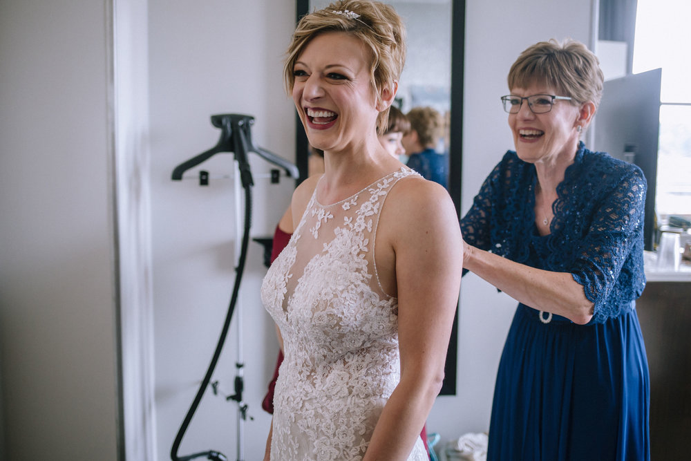 Bride getting ready in wedding dress for Pittsburgh wedding at Studio Slate planned by Exhale Events. Find more wedding inspiration at exhale-events.com!
