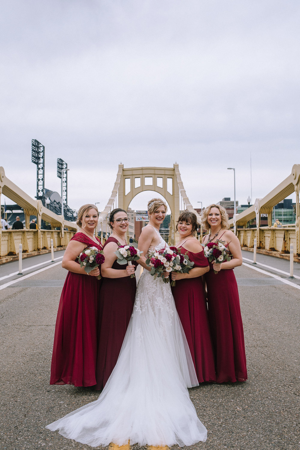 Bride poses for wedding photos with bridesmaids in red bridesmaids dresses for Pittsburgh wedding at Studio Slate planned by Exhale Events. Find more wedding inspiration at exhale-events.com!