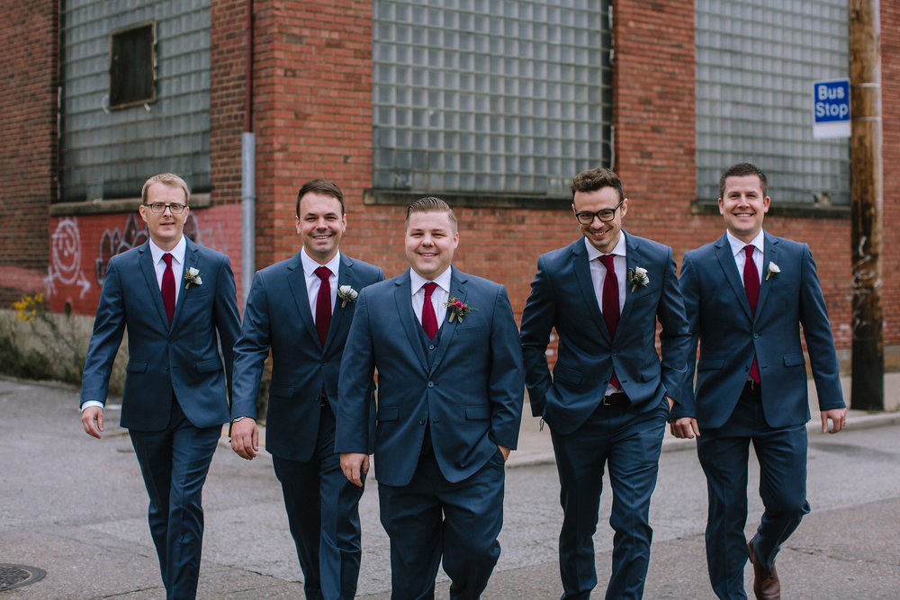 Groom poses with groomsmen for wedding photos in navy tuxedos for Pittsburgh wedding at Studio Slate planned by Exhale Events. Find more wedding inspiration at exhale-events.com!