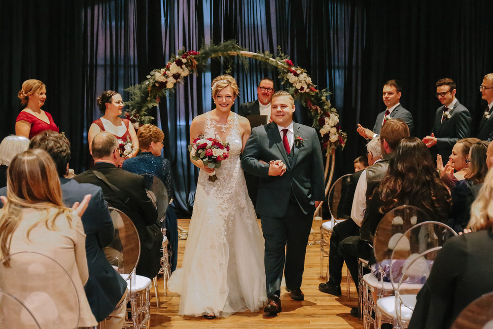Bride and groom celebrate after wedding ceremony at Pittsburgh wedding at Studio Slate planned by Exhale Events. Find more wedding inspiration at exhale-events.com!