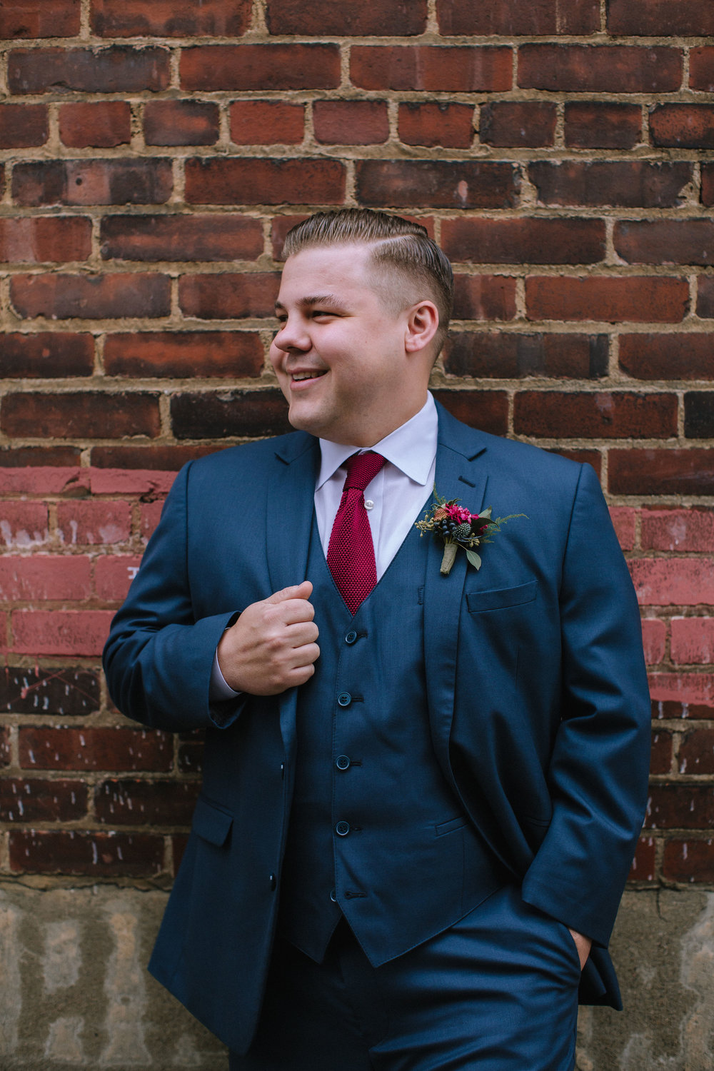 Groom poses in modern navy tuxedo with red tie for modern Pittsburgh wedding at Studio Slate planned by Exhale Events. Find more wedding inspiration at exhale-events.com!