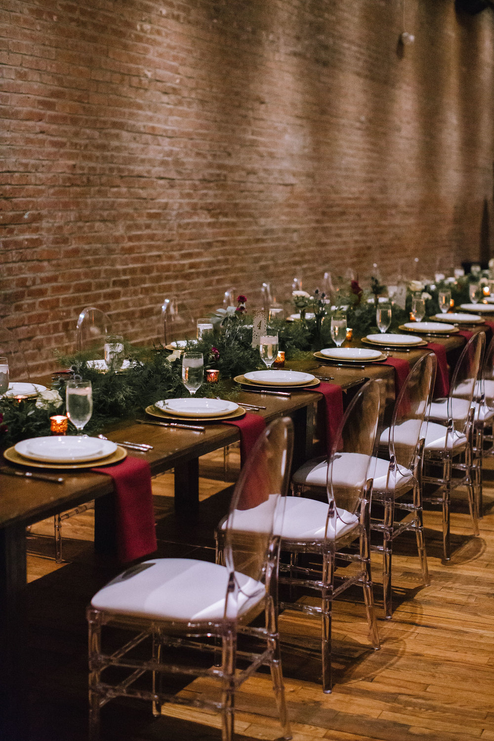 Wedding table setting and table decor with greenery and red and gold accents for Pittsburgh wedding at Studio Slate planned by Exhale Events. Find more wedding inspiration at exhale-events.com!