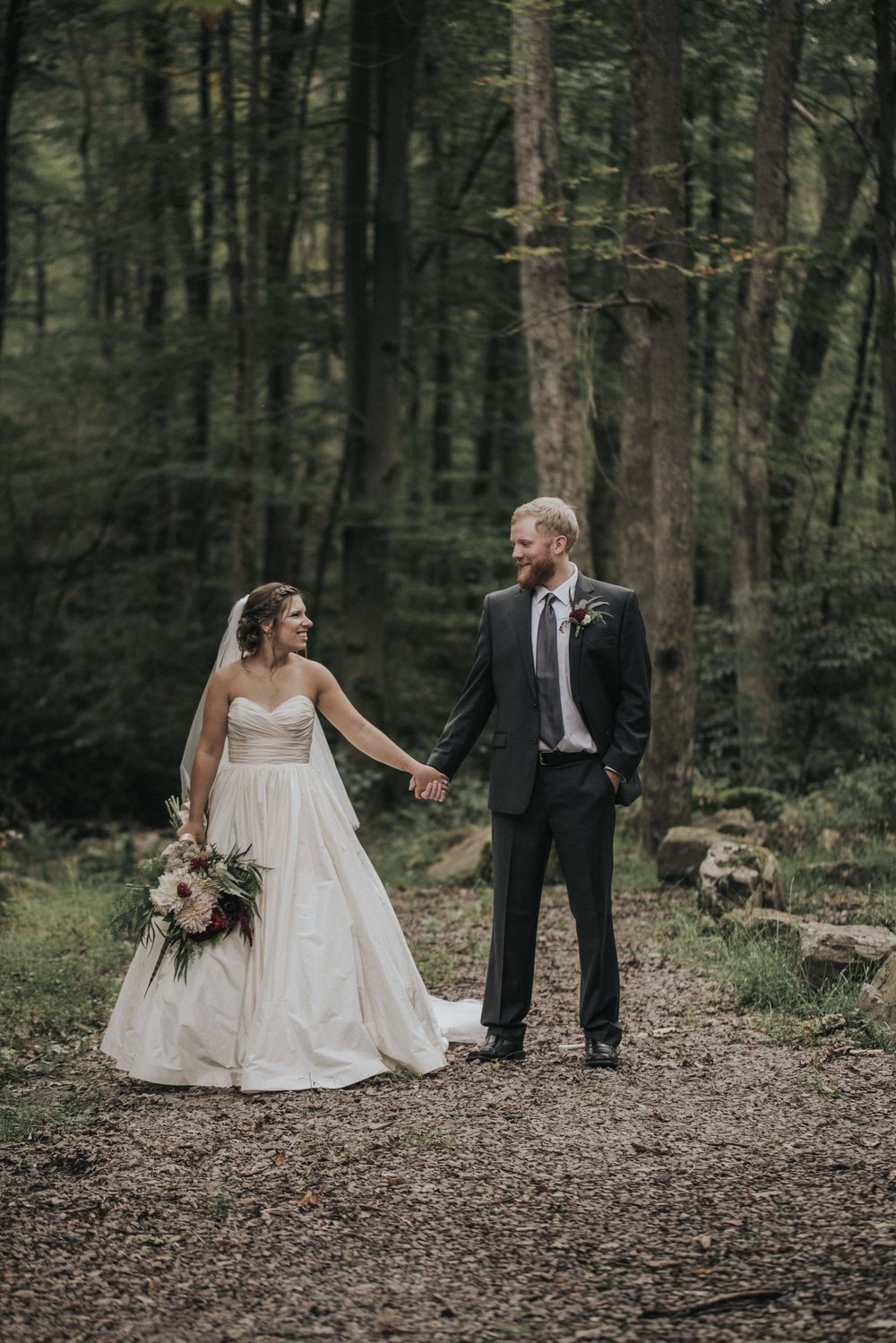 Bride and groom pose for wedding photos in the woods for rustic wedding in Farmington, PA planned by Exhale Events. Find more wedding inspiration at exhale-events.com!