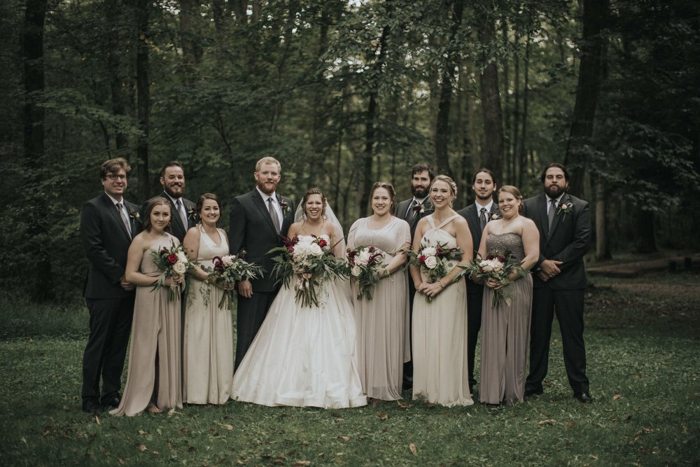 Bride and groom pose with wedding party for wedding photos in the woods for rustic wedding in Farmington, PA planned by Exhale Events. Find more wedding inspiration at exhale-events.com!