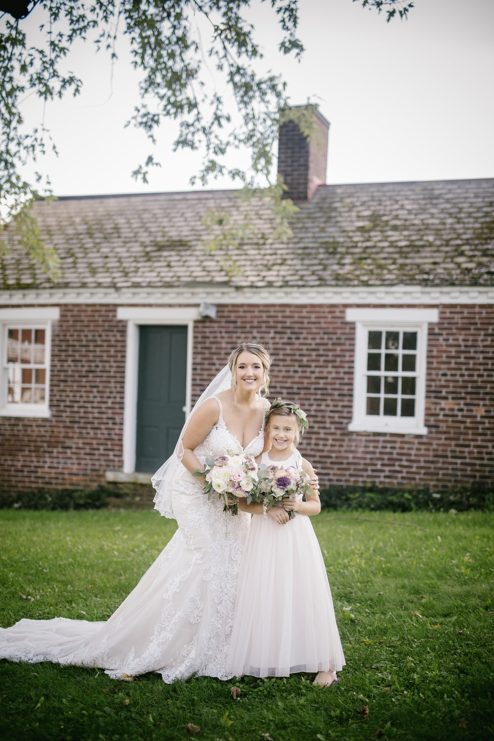 Bride poses for wedding photos in embellished lace wedding dress with flower girl for rustic wedding in Pittsburgh, PA planned by Exhale Events. Find more wedding inspiration at exhale-events.com!