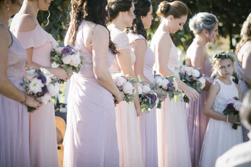 Bridesmaids at wedding ceremony in pink bridesmaids dresses for rustic wedding in Pittsburgh, PA planned by Exhale Events. Find more wedding inspiration at exhale-events.com!