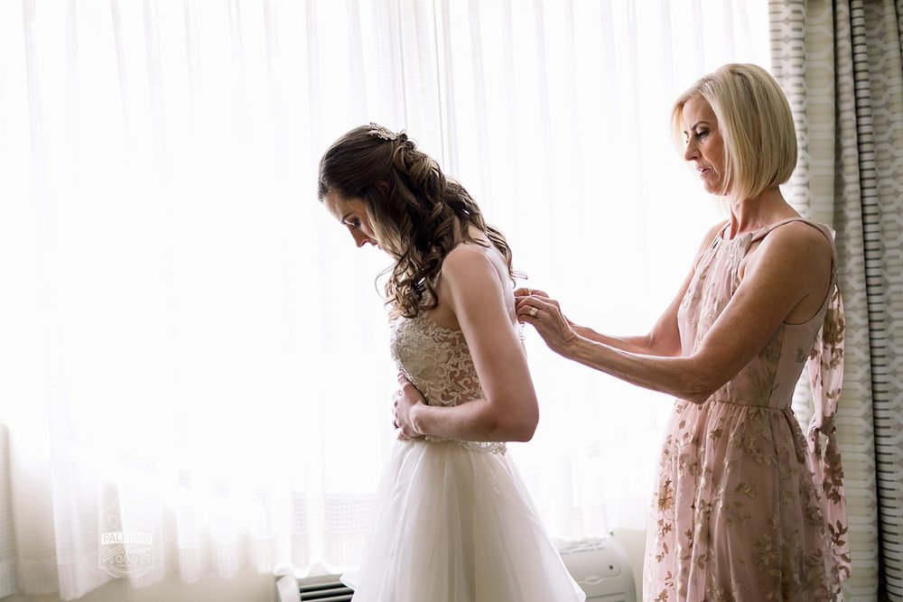 Bride getting into wedding dress for fall barn wedding in Pittsburgh, PA planned by Exhale Events. Find more wedding inspiration at exhale-events.com!