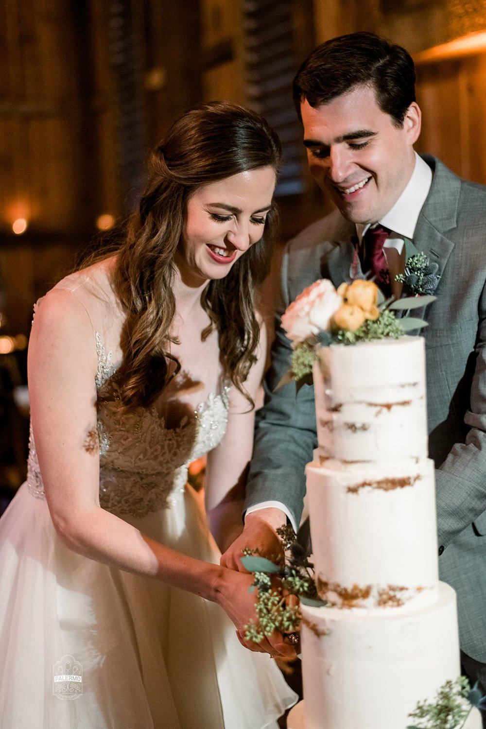Bride and groom cut wedding cake at fall barn wedding in Pittsburgh, PA planned by Exhale Events. Find more wedding inspiration at exhale-events.com!