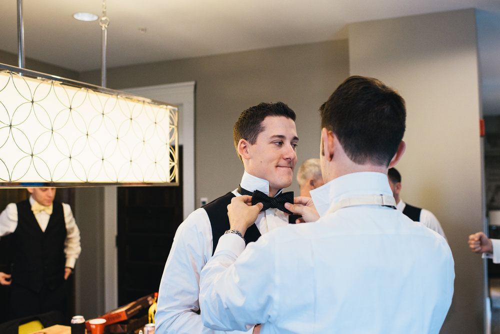 Groom and groomsmen getting ready in their wedding attire for black, white, and gold wedding in Buffalo, NY planned by Exhale Events. Find more wedding inspiration at exhale-events.com!