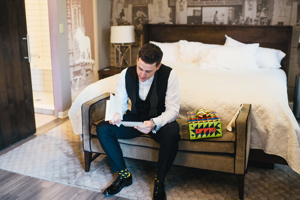 Groom reading letter from bride before their black, white, and gold wedding in Buffalo, NY planned by Exhale Events. Find more wedding inspiration at exhale-events.com!