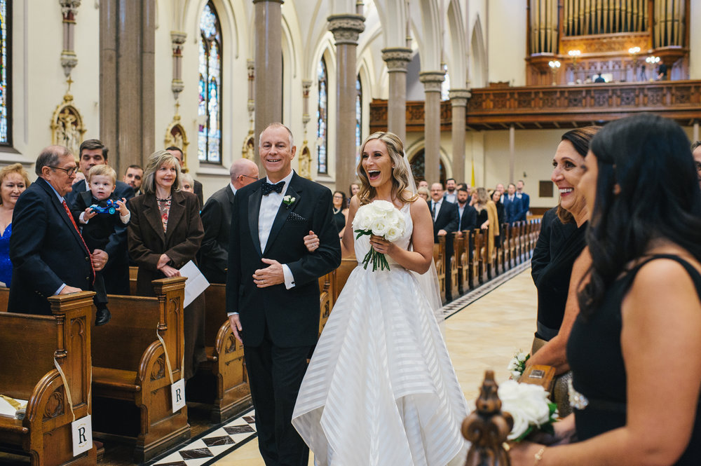 Bride walks down the aisle with her father at the wedding ceremony for black, white, and gold wedding in Buffalo, NY planned by Exhale Events. Find more wedding inspiration at exhale-events.com!