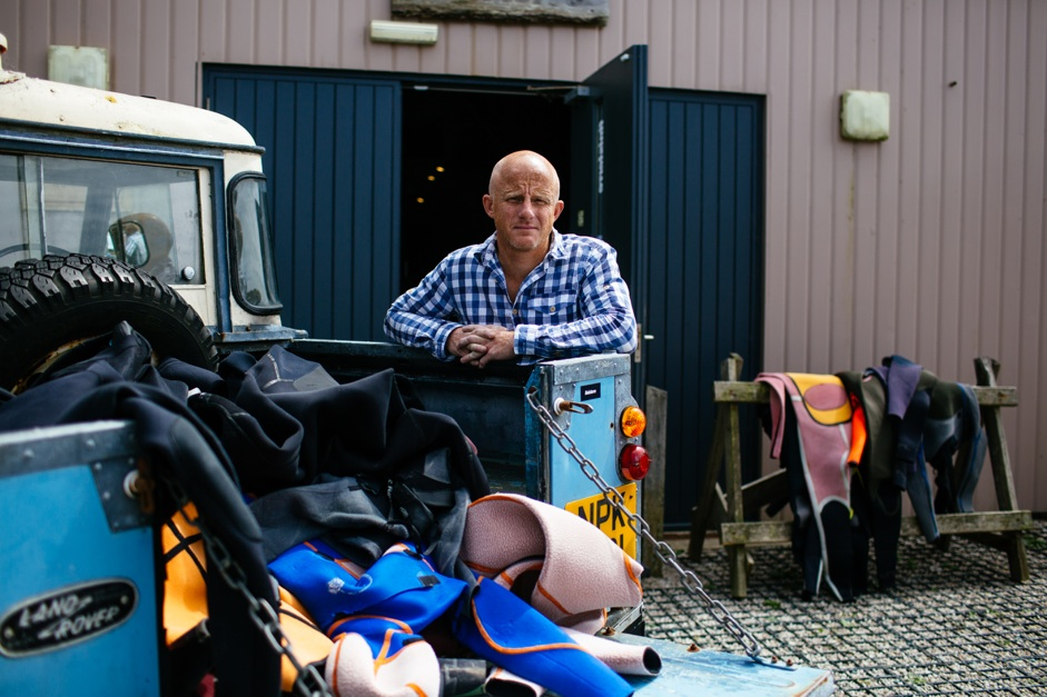 Tom Kay, Founder or Finisterre with a handful of used wetsuits