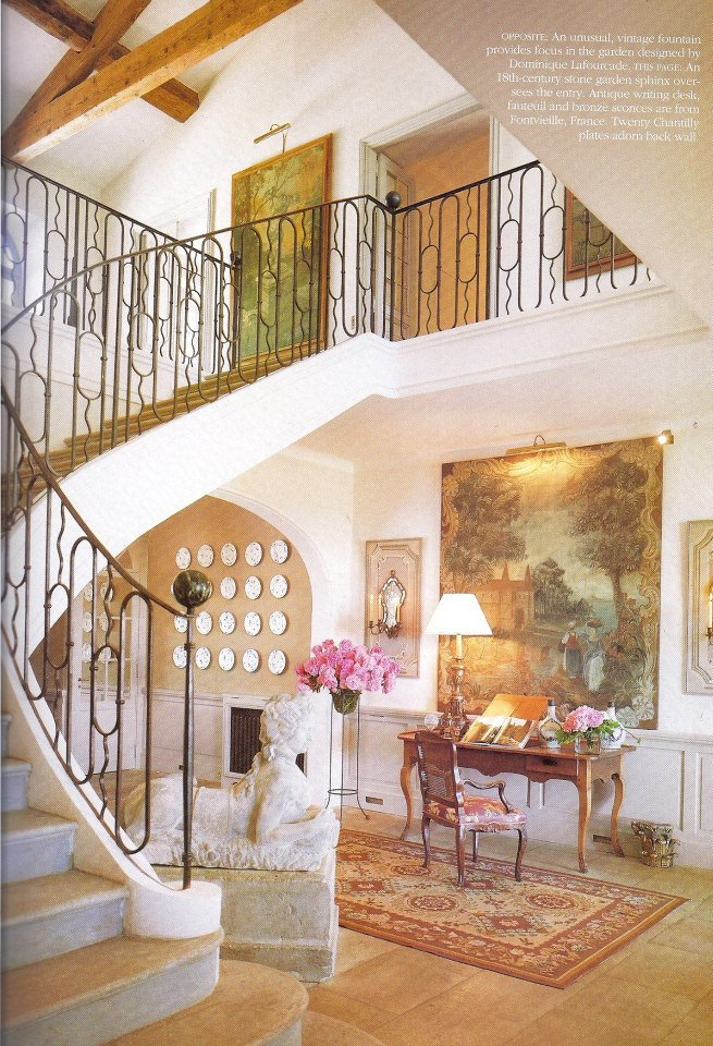 Spiraling staircase with sculpture and writing desk in French entry way.