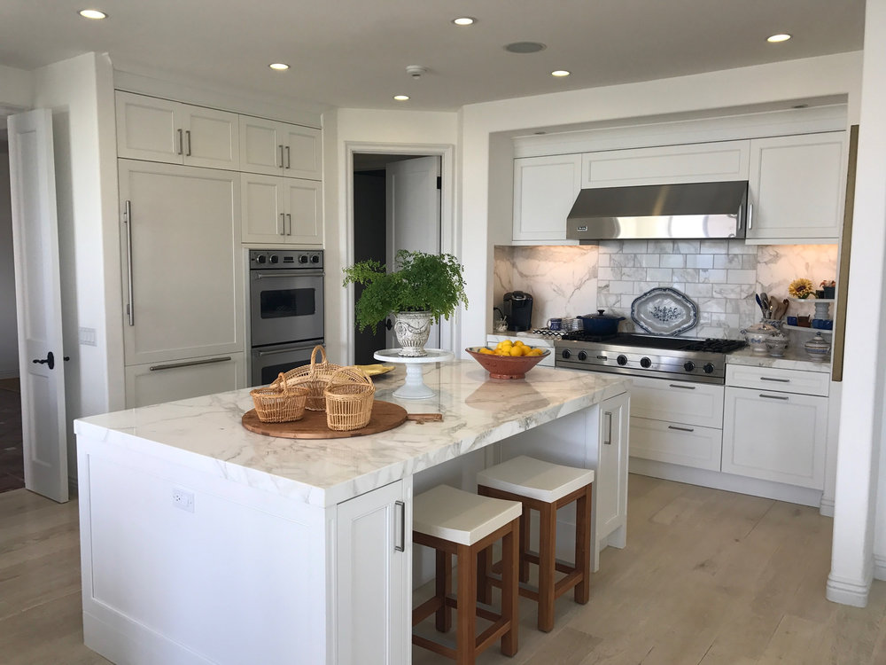 Kitchen design with marble counters and marble backsplash.
