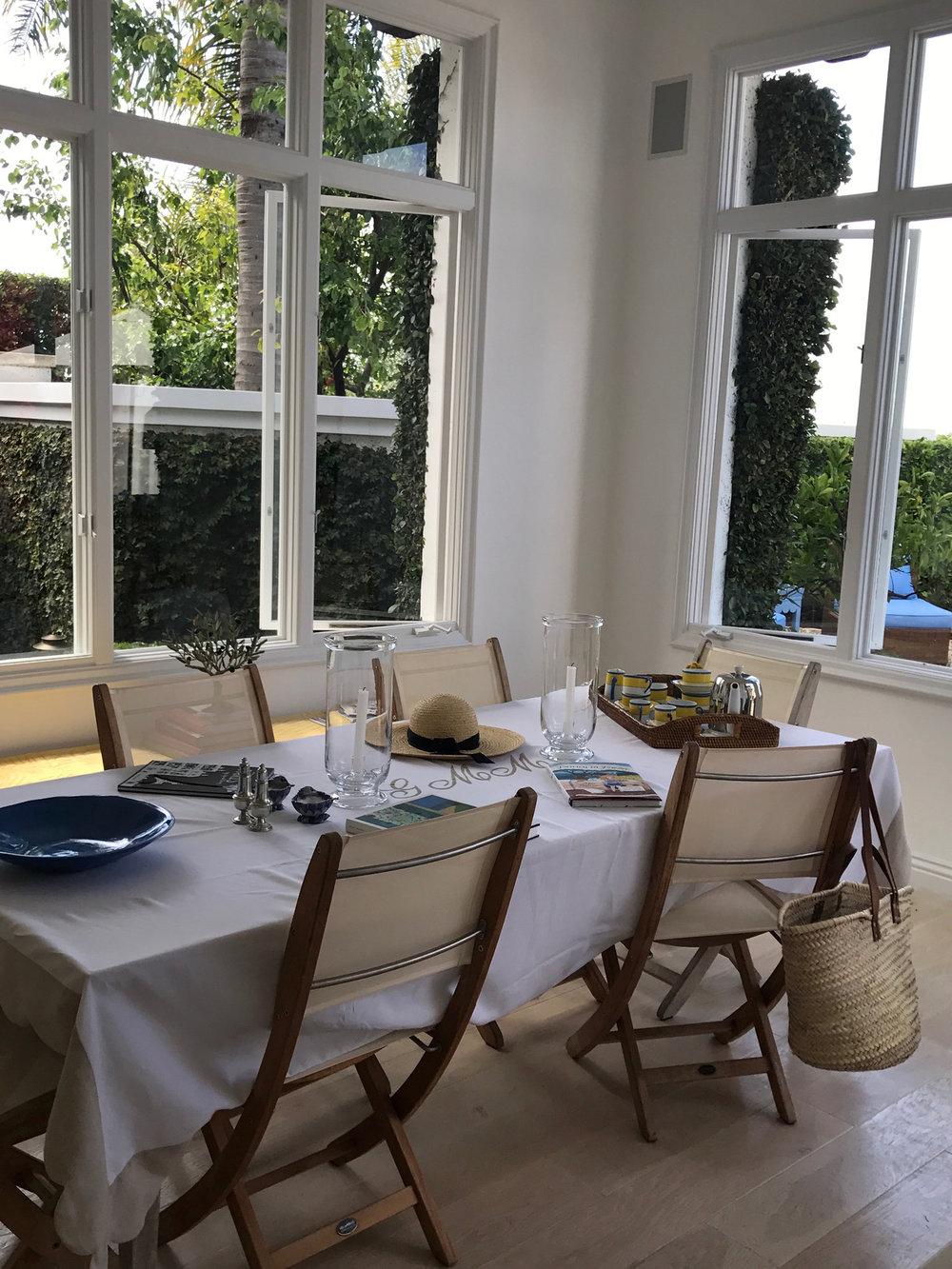 Laguna beach kitchen table with windows looking onto patio.