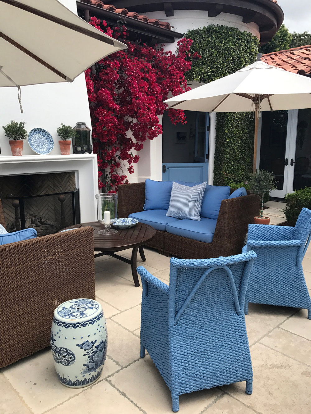 Indoor Outdoor Patio in Laguna Beach home, arched doorway with blue chairs and pillows.