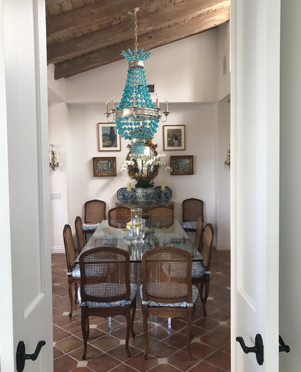 Laguna beach dining room of home designer Ginny Magher, tiled floors, wood ceiling, French design.