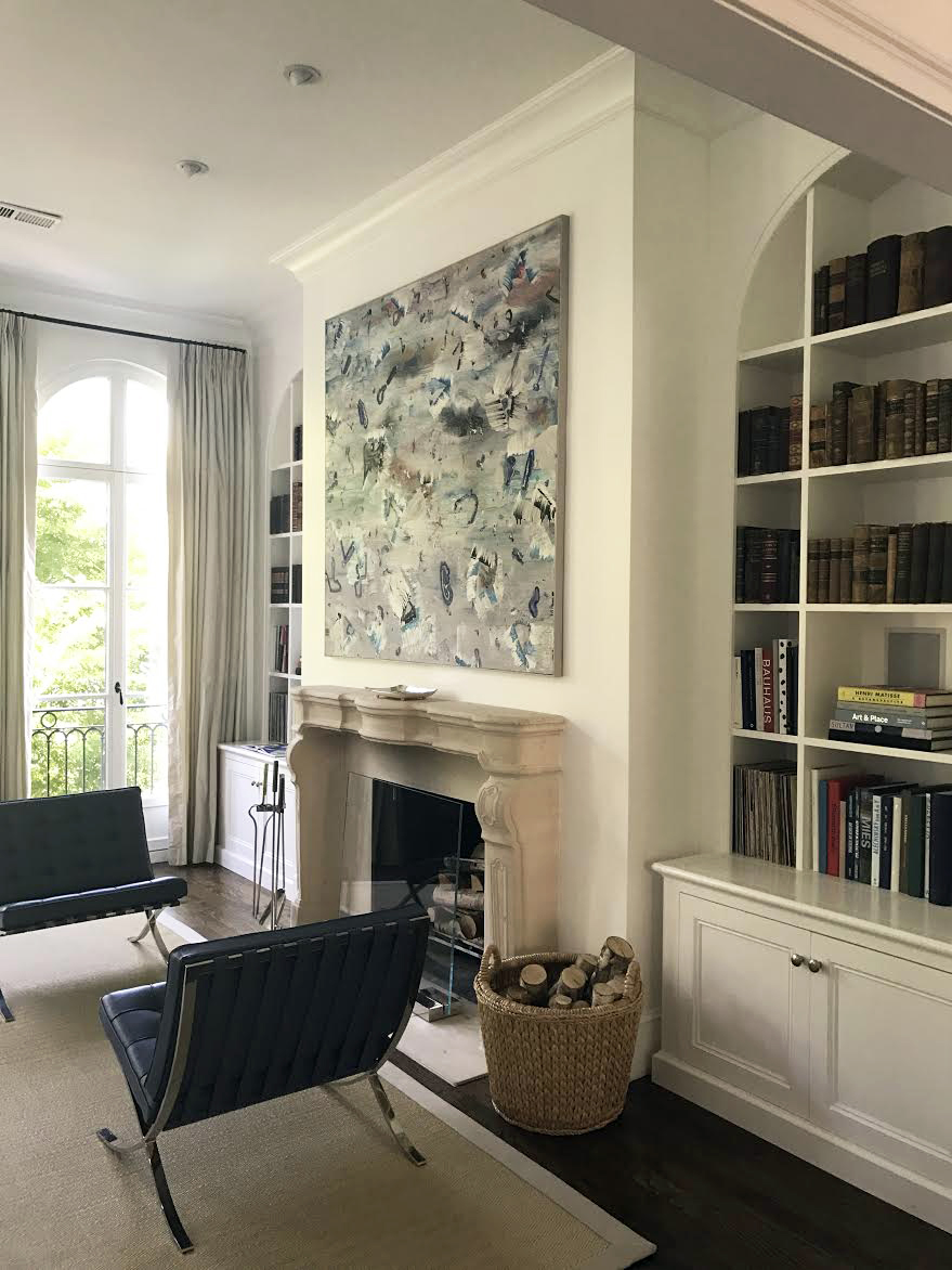 French living room design with contemporary art and large windows. Rounded inlaid bookshelf.