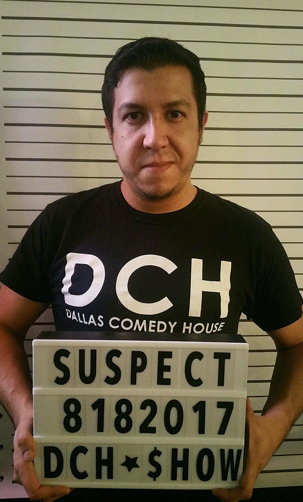 Carlos wearing a real intern shirt while taking a fake mugshot.
