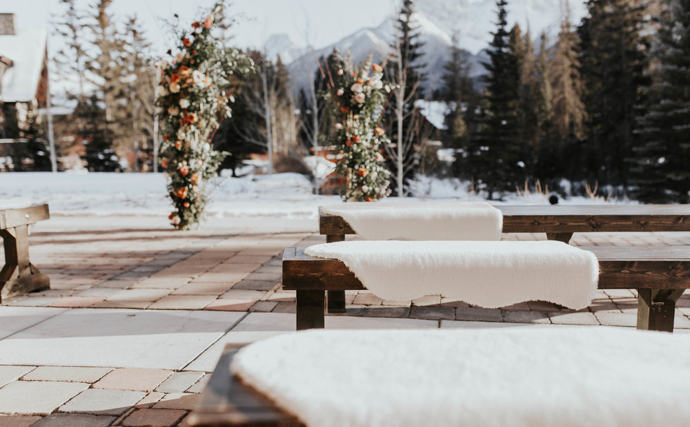 Outdoor wedding ceremony at the Malcolm Hotel in Canmore with wooden benches, Flowers by Janie.jpg