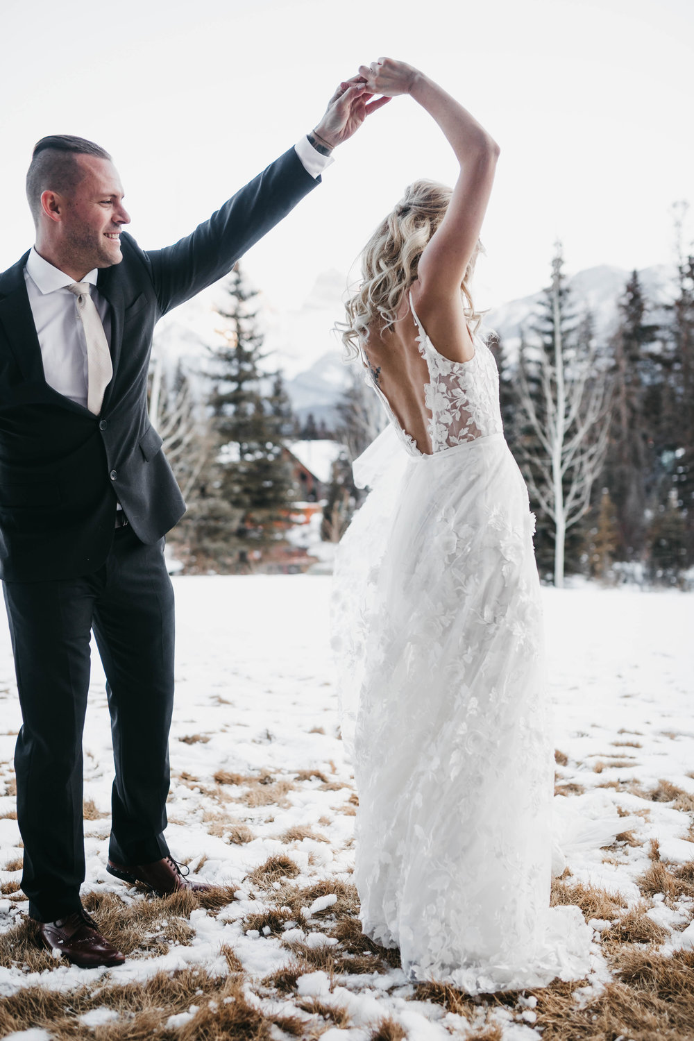Winter wedding Canmore bride and groom twirling in the snow, Malcolm hotel wedding.jpg