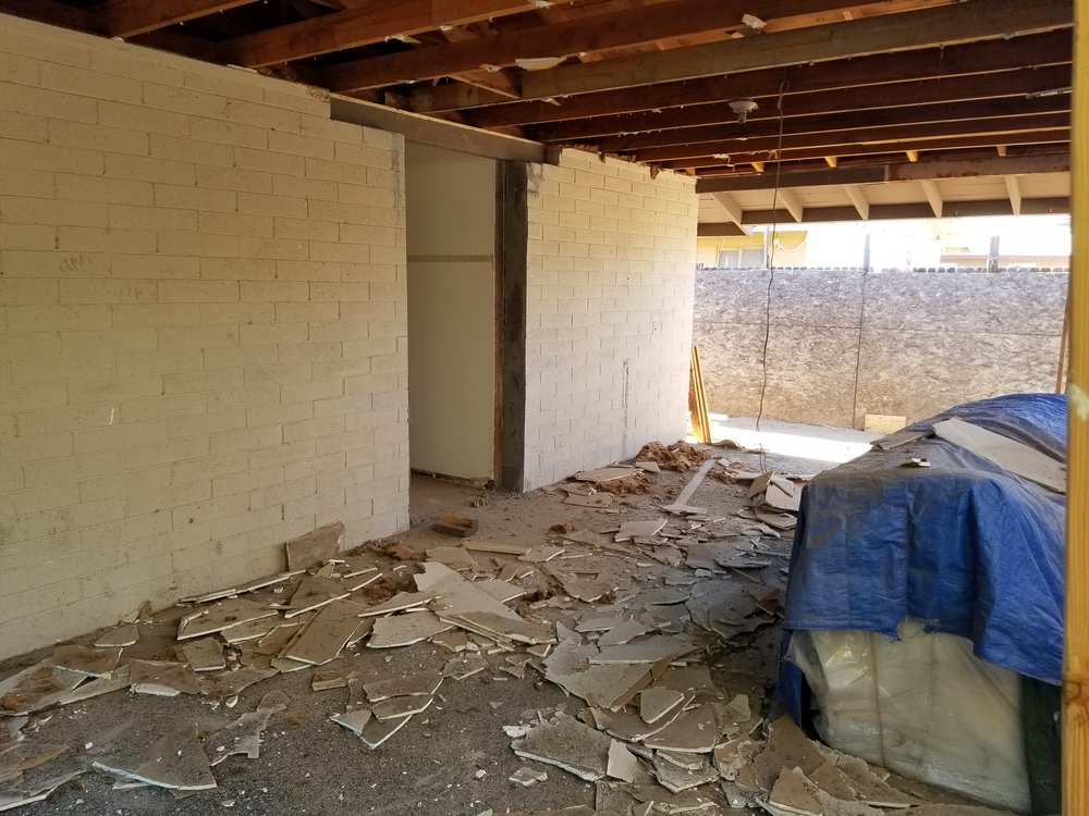 Carport ceiling demolition and cutting the doorway into the cinder block wall.