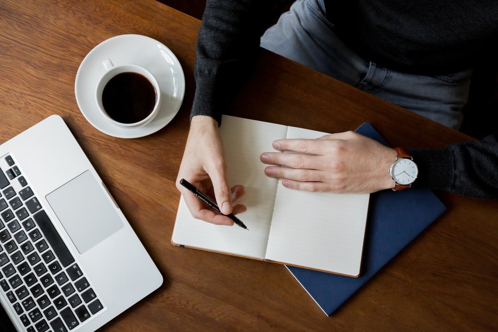 styled-lifestyle-stock-photo-of-a-man-at-a-dark-wooden-desk-at-home-or-cafe-writing-in-a-notebook-a_t20_oolzmx.jpg