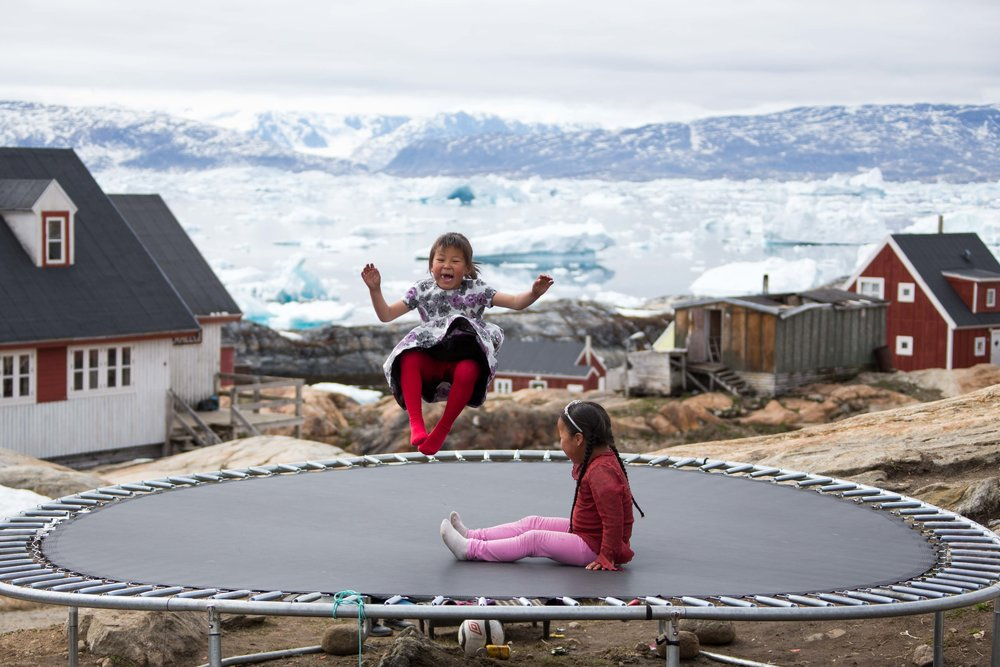 Tunu girls play happily on a public trampoline in the settlement of Tiniteqilaaq with an ice fjord behind them, East Greenland.